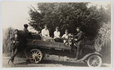Portrait of a group of men and women in a vehicle.