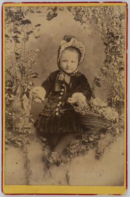 Young child holding a basket of flowers