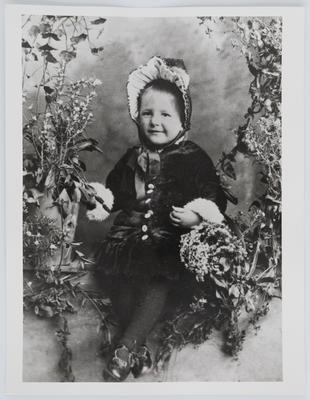 Studio portrait of Edith Collier as a child, surrounded by flowers