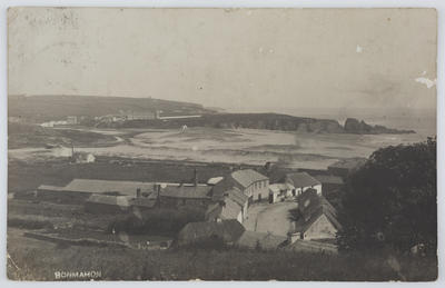 Black and white photographic postcard of Bonmahon, Ireland showing the village and coast from a hillside above the village.