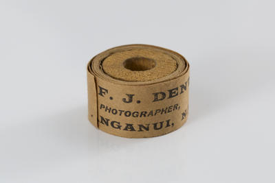 """Frank Denton; One roll of brown tape (inscribed """"From F.J. DENTON, PHOTOGRAPHER, WANGANUI, N.Z.""""); L1996/11/37"""