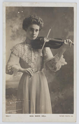 Black and white photographic postcard featuring the violinist Miss Marie Hall. Addressed to Edith Collier from Minnie.