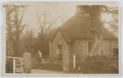 Unknown; Black and white photographic postcard of a thatched house and two women.; 23 Dec 1918; A2015/1/176