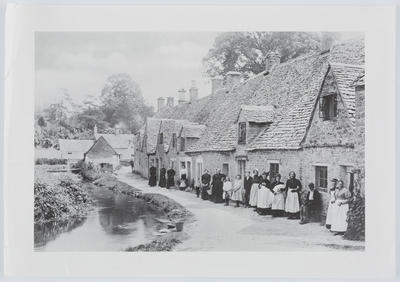 Unknown; A black and white photo-mechanical print of a group of people standing in front of a row of houses.; A2015/1/177
