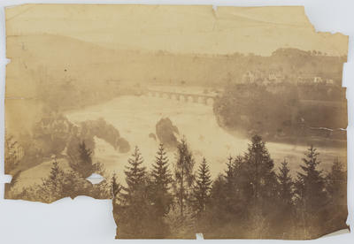 Unknown; A faded sepia photographic print of a landscape. Behind is a river with bridge and a small town on right.; A2015/1/178
