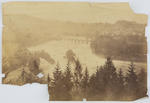 A faded sepia photographic print of a landscape. Behind is a river with bridge and a small town on right.